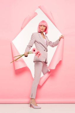 Stylish woman in suit and pink wig holding flowers and posing in torn paper, on white stock vector