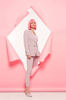 Fashionable beautiful girl in suit and pink wig posing in torn paper, on white stock vector