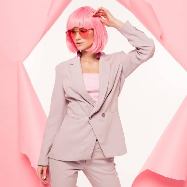 Fashionable girl in suit, sunglasses and pink wig posing in torn paper,  isolated on white stock vector