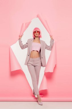 Stylish girl in trendy suit, sunglasses and pink wig posing in torn paper, on white stock vector