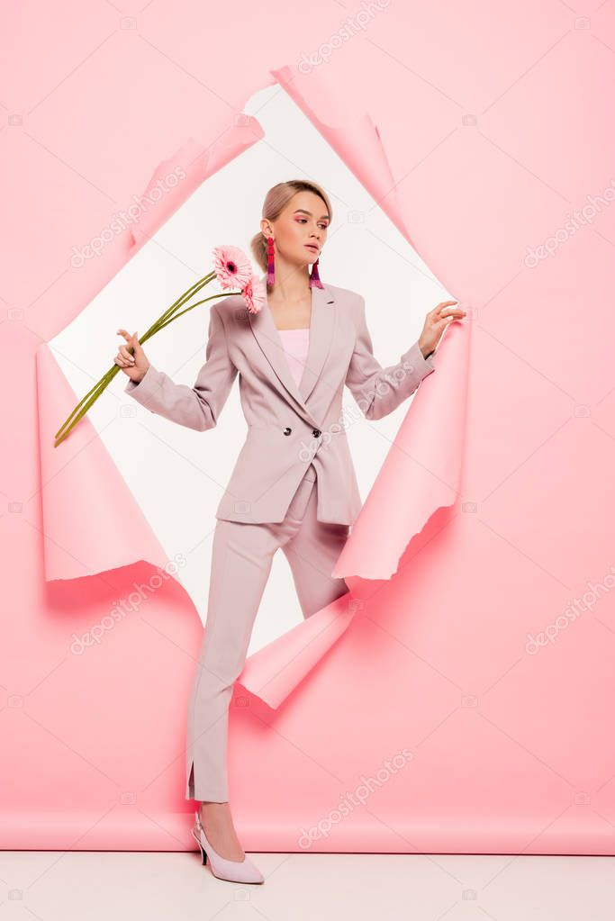 Attractive girl in trendy suit holding flowers and posing in torn paper, on white stock vector