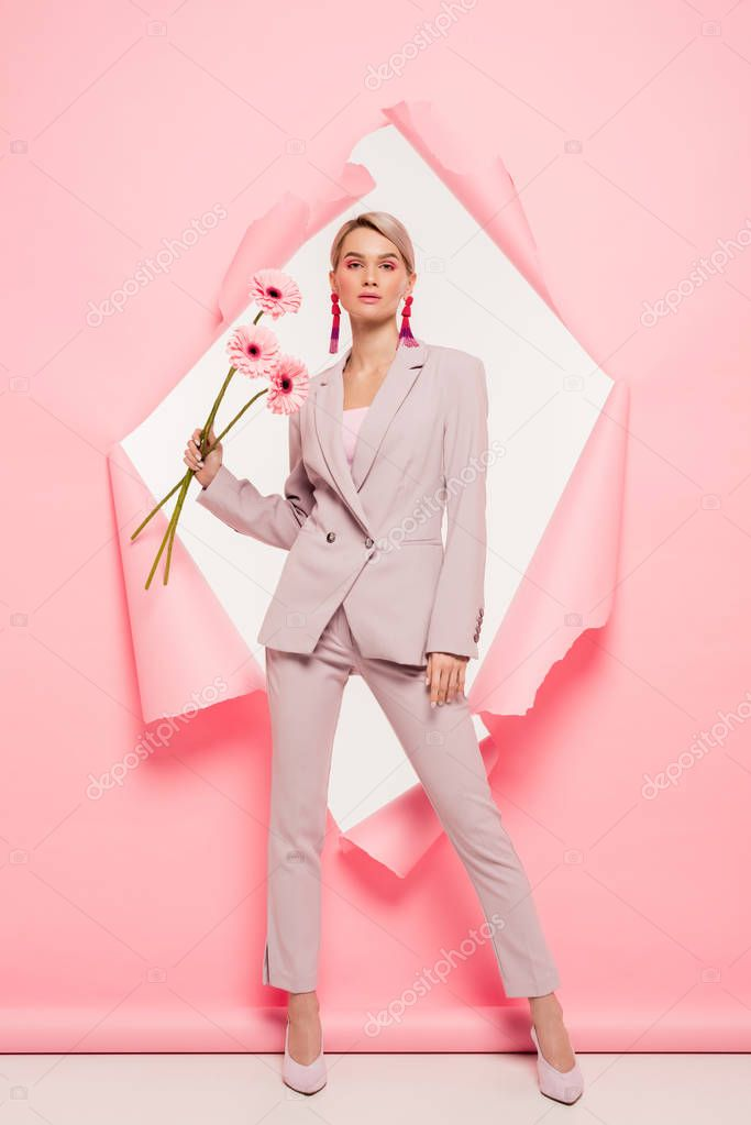 Beautiful girl in fashionable suit holding flowers and posing in torn paper, on white stock vector