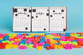 Kalendář a barevné plastové čísla na modrém pozadí