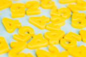 Selektivní zaměření žlutých plastových čísel na modrém pozadí