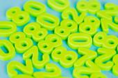 Selektivní zaměření zelených plastových čísel na modré pozadí