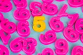 Žlutá pět čísel a růžová plastová čísla na modrém pozadí