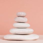 Fotografie Detailní pohled na skládané zenové kameny na písku izolovaném na broskvi