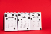 Paper calendar with autumn months on red background