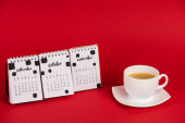 Calendar with autumn months and coffee cup on red background