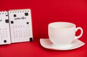 Selektivní zaměření šálku kávy a kalendáře na červené pozadí