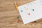 Vysokoúhlý pohled na tužku, kancelářské kolíky a kalendář duben na dřevěném pozadí
