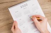 Oříznutý pohled na datum poznámky muže s tužkou na kalendáři na dřevěném pozadí