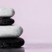 Zblízka pohled na mokré zenové kameny na skle s kapkami vody izolovanými na fialové