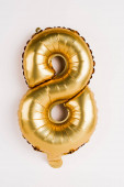 Decorative golden balloon in shape of eight on grey background