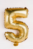 Photo Golden balloon in shape of five number on grey background