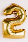 Photo Golden balloon in shape of two number on grey background