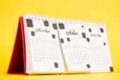 Selective focus of october on paper calendar on yellow background