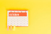 Top view of pencil, calendar with october month and sticky notes on yellow background