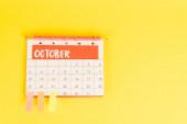 Horní pohled na tužku, kalendář s říjnovým měsícem a lepicí poznámky na žlutém pozadí