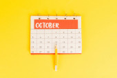 Top view of pencil on calendar with november month on yellow background
