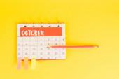 Horní pohled tužky na kalendář s listopadovým měsícem a lepicí poznámky na data na žlutém pozadí