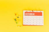 Horní pohled na kalendář s měsíc říjen a kancelářské špendlíky na žlutém pozadí