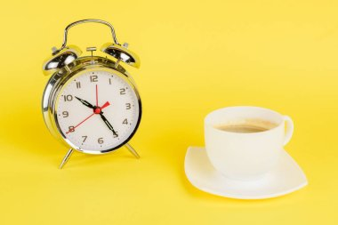 Silver alarm clock and cup of coffee on yellow background stock vector