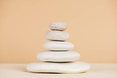 Close up view of stacked zen stones on sand isolated on beige stock vector
