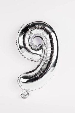 Silver balloon in shape of nine number on grey background