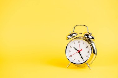 Silver alarm clock on yellow background
