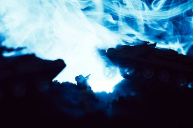 Toy tanks and soldier with blue smoke on black background, battle scene