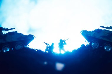 Battle scene of toy warriors and tanks with smoke on blue background