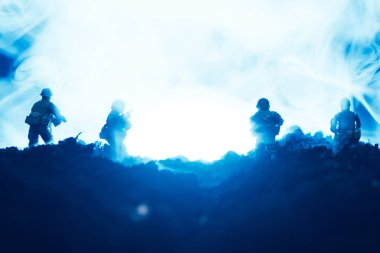 Battle scene with toy warriors in smoke on blue background