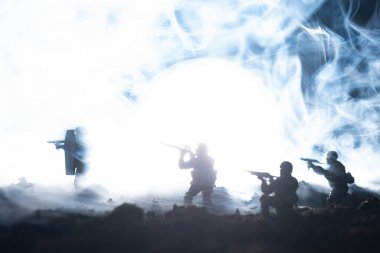 Battle scene with toy soldiers in smoke on black background