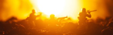 Battle scene of toy soldiers with sun on orange background, panoramic shot