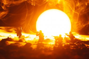 Battle scene of toy soldiers in smoke with sunset at background
