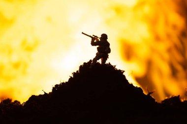 Battle scene with toy warrior on battleground and fire at background
