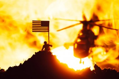 Battle scene with toy warrior near american flag and helicopter in fire with sunset at background