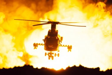 Battle scene with toy helicopter and fire at background