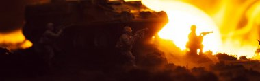 Battle scene with toy warriors, tank and fire with sunset at background, panoramic shot