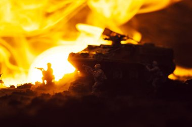 Toy soldiers with tank, fire and sunset on black background, battle scene