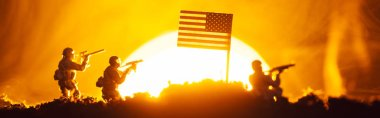 Battle scene with toy warriors near american flag in smoke with sunset at background, panoramic shot