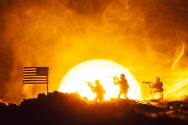 Battle scene of toy soldiers, american flag and fire with sunset at background