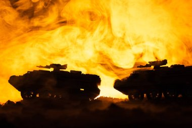 Battle scene with toy tanks and fire at background