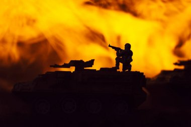 Battle scene with silhouettes of toy warrior and tanks with fire at background