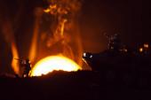 Bitevní scéna s hračkou bojovníci a tank v kouři se západem slunce na pozadí