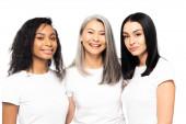 veselé multikulturní ženy při pohledu na kameru izolované na bílém