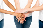 cropped view of multicultural women putting hands together isolated on white