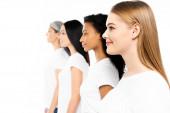 boční pohled na šťastné multikulturní ženy v bílých tričkách izolovaných na bílém