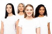 four happy multicultural women in white t-shirts looking at camera isolated on white